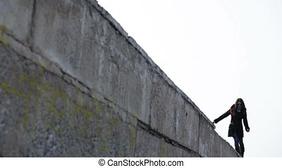 A woman walks along the edge of the wall neglecting safety