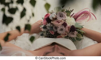 Beautiful bride lying in the boat with bouquet in hands -...