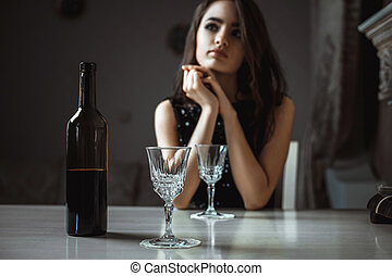 beautiful brunette girl sitting at a table in the restaurant with wine
