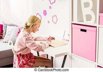 Smart girl in room - Smart little girl doing her homework in...