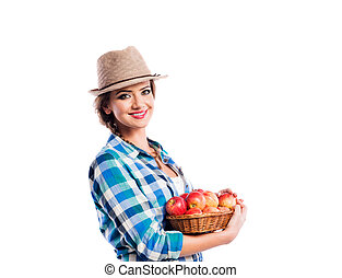 Woman, checked shirt holding basket with apples. Autumn harvest