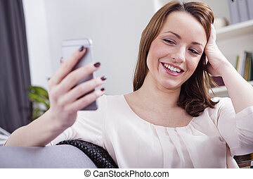 Attractive smiling young girl videochatting with smartphone...