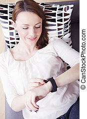 Smiling young girl taking a look on her smart watch while...