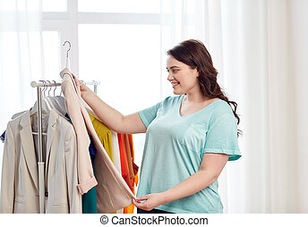 happy plus size woman choosing clothes at wardrobe