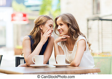 young women drinking coffee and talking at cafe - people,...