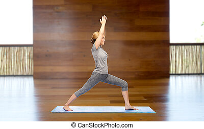 woman making yoga warrior pose on mat - fitness, sport,...