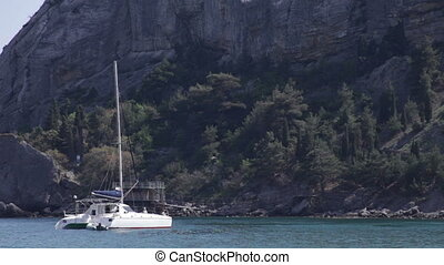 yacht in the bay near cliff - yacht in the bay near the...