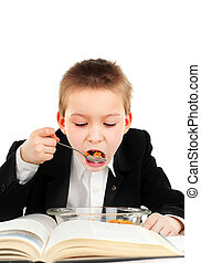 Schoolboy eat in the Classroom - Hungry Kid eating on the...