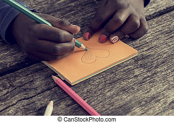 Closeup of African-American girl drawing and coloring a...