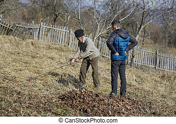 Old farmer teaching grandson - Old farmer showing his...