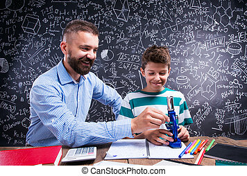 Hipster teacher with his student with microscope, big...