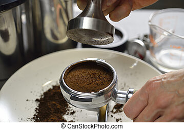 Coffee - Barista using a tamper to press ground coffee into...