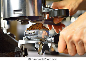 Coffee grinder grinding freshly roasted coffee beans into a...