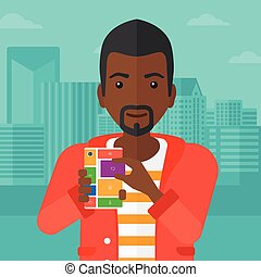 Man with modular phone - An african-american man holding...