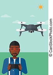 Man flying drone - An african-american man flying drone with...