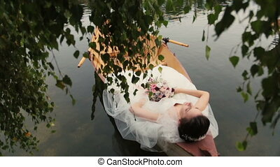 Charming brunette bride lying in the canoe with bouquet in...