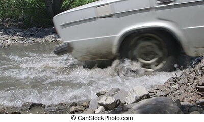 Wheels of car VAZ 2106 splashing water crossing creek...