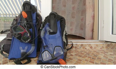 Two backpacks with snorkeling gear at entrance to hotel room...