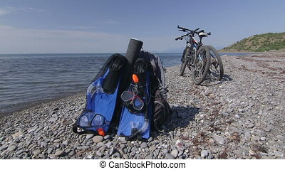 Two mountain bikes and backpacks with snorkeling sets on wild pebble beach