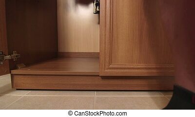 Man with bare legs hiding in a wardrobe