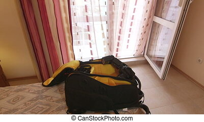 Opened professional photo backpack with camera on bed in...