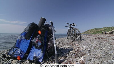 Two mountain bikes backpacks with snorkeling sets and action...