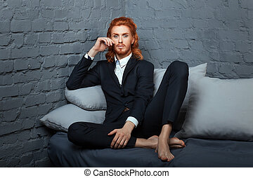 On the sofa sits cross-legged guy On his head red hair and a...