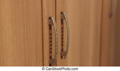 Close-up of female hands opening doors of wooden wardrobe