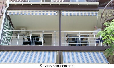 Shading balcony of summer hotel man unrolling retractable awning on a sunny day