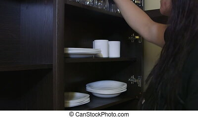Maid cleaning hotel room placing white plates and cups on a...