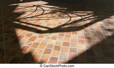 Shadows on terrace ceramic tiled floor in sunny day