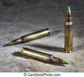 Ammo - Green tipped rifle bullets that are on a stone...