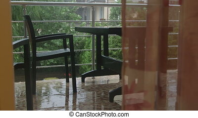 Balcony with wet outdoor table and chairs during heavy rain...