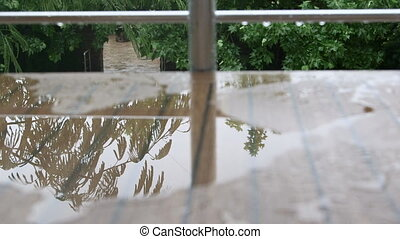 Balcony and puddle of rain water on wet table