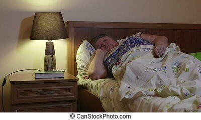Overweight older woman lying in bed talking on phone at...