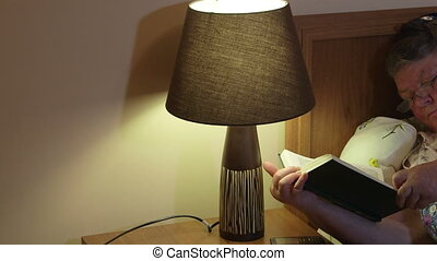 Older woman lying in bed reading book before dozing off at...