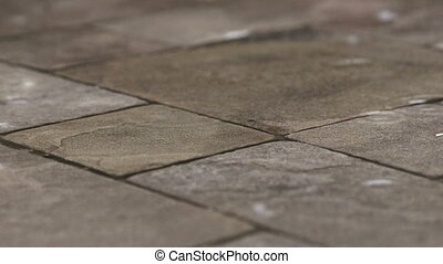 Rain drops rippling in a puddle on wet garden stone paving...