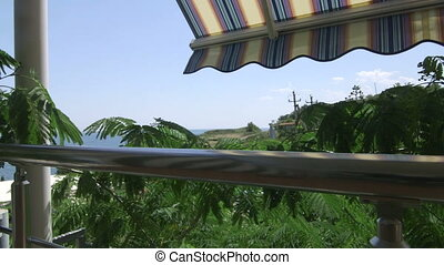 Shaded balcony of summer beach hotel in cooling shade of striped awning