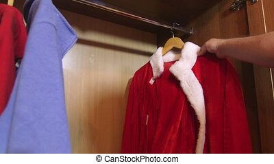 Santa Claus suit on a hanger hanging in closet