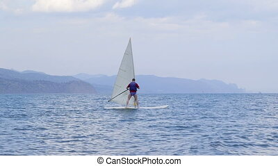 Man getting windsurfing lessons along shoreline in a sea