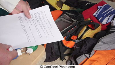 Man with checklist packing bag on bed for travel vacation
