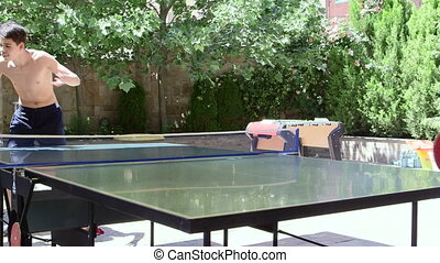 Teenage boys have fun playing outdoor table tennis in the...