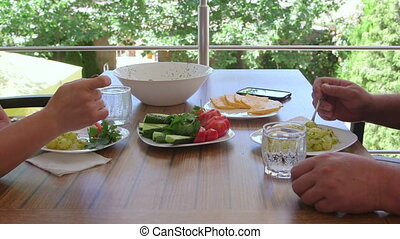 Adult couple man and woman having outside light lunch on the balcony