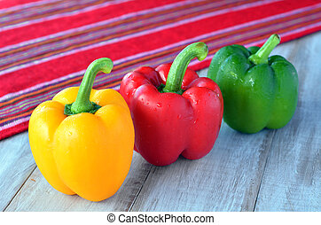 Yellow, red and green capsicum on a wooden table - yellow,...