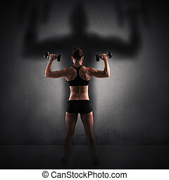 Strength and power - Muscular woman looks at her big shadow