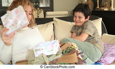 Cute boy offering gift - Happy mother receivinga gift box, a...
