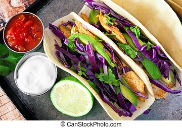 Spicy fish tacos with red cabbage slaw, avocado and lime...