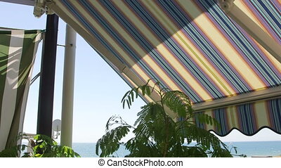 Terrace with retractable striped awnings with sea view in a...