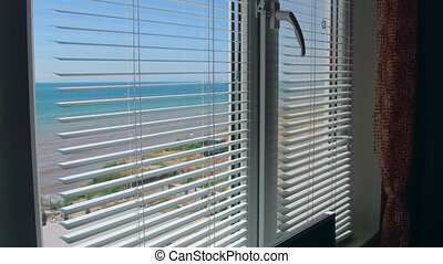 View from the open window with blinds on the sea in summer
