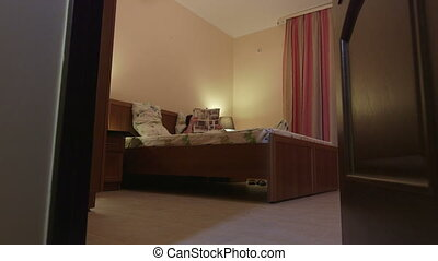 open door to bedroom of hotel room woman lying on bed...